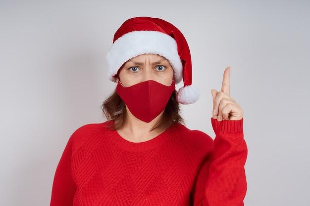 La donna arrabbiata in una maschera protettiva rossa, in un cappello da babbo natale su uno sfondo grigio mostra un gesto di attenzione.