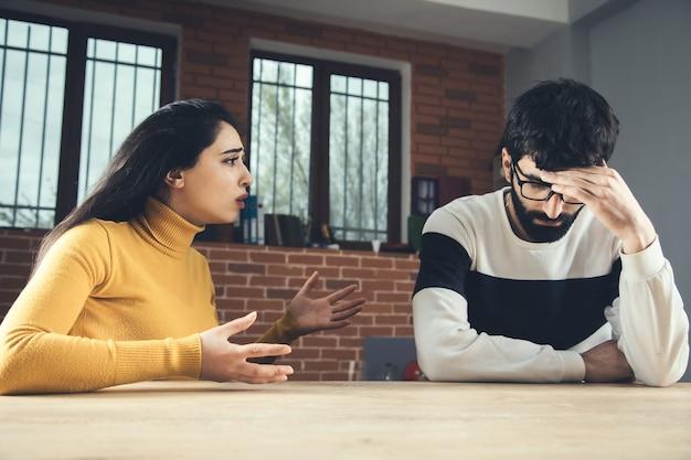 Donna arrabbiata e uomo triste sul tavolo