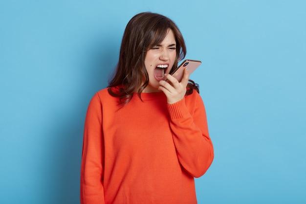 Donna arrabbiata che grida mentre parla tramite telefono, essendo molto arrabbiata, indossando abbigliamento casual arancione, in piedi isolato