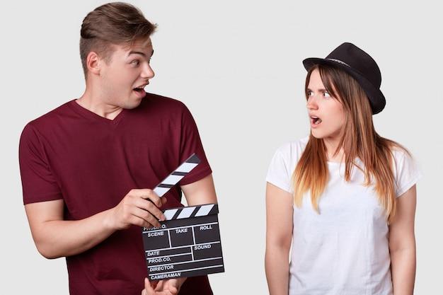 La donna arrabbiata in copricapo alla moda guarda il suo produttore che detiene il ciak, ha un'espressione scioccata, suggerisce una nuova scena Foto Premium