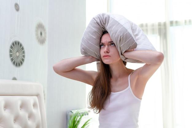 Donna arrabbiata che soffre e disturbata dai vicini rumorosi e che copre le orecchie di cuscino mentre cerca di cadere nel letto di casa