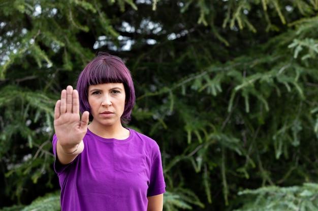 Donna arrabbiata con in viola che mostra il palmo della mano dicendo stop