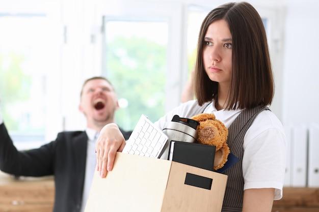Capo urla arrabbiato che indica il braccio per licenziare il lavoratore triste con il ritratto della scatola di roba.