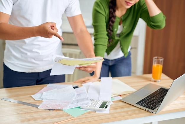 Giovani coppie arrabbiate che discutono dai loro molti debiti a casa