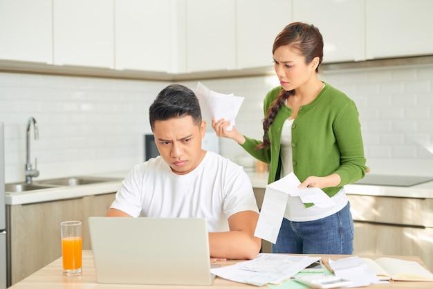 Giovani coppie arrabbiate che gridano in una lite dura dai loro molti debiti a casa. concetto di problemi familiari finanziari.