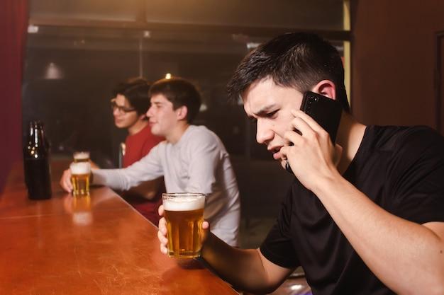 Un giovane arrabbiato discute al telefono mentre i suoi amici ubriachi si godono una birra al bar.