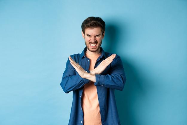 Giovane arrabbiato che aggrotta le sopracciglia e stringe i denti indignato, mostrando il gesto trasversale per fermare o vietare qualcosa, in piedi su sfondo blu.