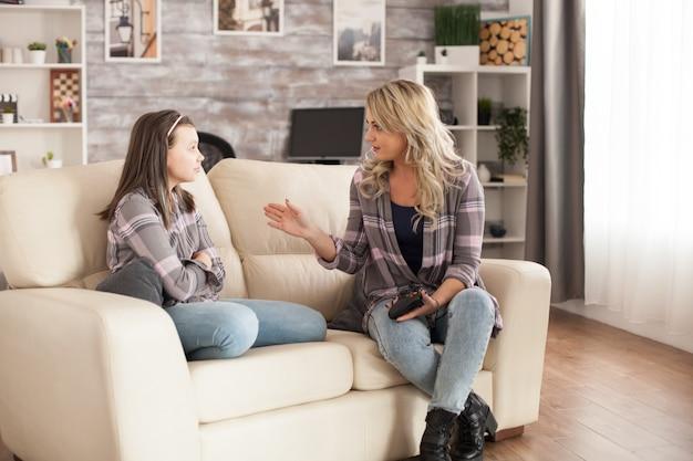 Giovane madre arrabbiata con la sua piccola figlia perché sta giocando a troppi videogiochi.