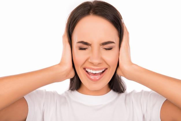 Giovane donna arrabbiata tappando le orecchie con le mani e urlando
