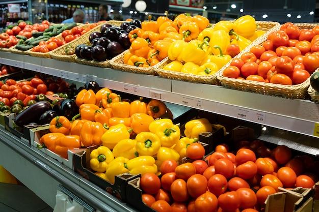 Vista angolare del bancone del supermercato con cestini di vimini e scatole con linguette con pomodori, peperoni e melanzane arancioni e gialli