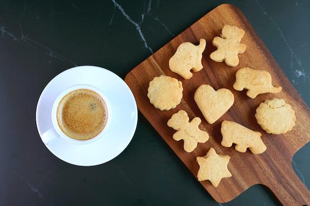 Biscotto a forma di animale ea forma di cuore con una tazza di caffè sulla tavola nera