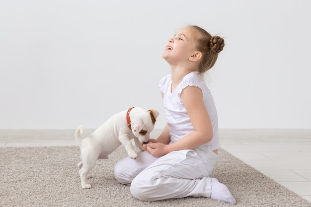Concetto di animali, bambini e animali domestici - bambina bambino seduto sul pavimento con cucciolo carino e giocando.