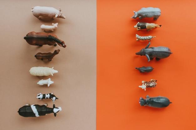 Gli animali che vivono nella fattoria stanno di fronte agli animali selvatici su uno sfondo rosso-marrone.