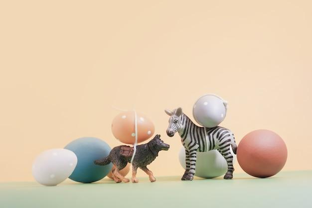 Animali (miniatura) che trasportano le uova di pasqua anno nuovo e sfondo vintage.
