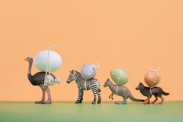 Animali (in miniatura) che trasportano le uova di pasqua. anno nuovo e vintage