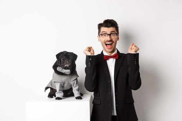 Concetto di animali, festa e celebrazione. felice giovane uomo in tuta e cucciolo in costume da compagnia in piedi sopra bianco, proprietario del cane che si rallegra e trionfa.