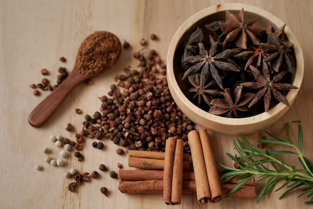 Anice e spezie in una tazza di legno con sfondo nero, concetto industriale