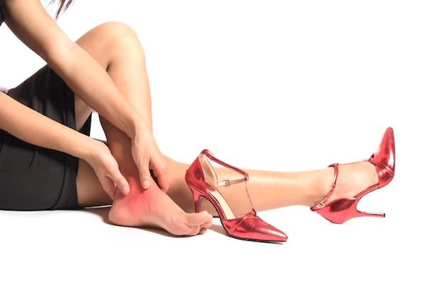 Distorsione alla caviglia su sfondo bianco giovane donna dolore con infiammazione caviglia destra