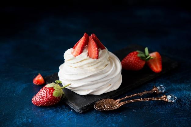 Torta anna pavlova con panna e fragole fresche su fondo scuro Foto Premium
