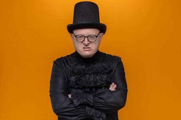Uomo adulto infastidito con cappello a cilindro e occhiali in camicia gotica nera incrociando le braccia e guardando