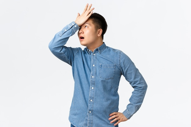 Il libero professionista maschio asiatico infastidito e infastidito dimentica qualcosa, alza gli occhi al cielo irritato e prende a pugni la fronte, facendo il gesto del palmo mentre ascolta un'offerta zoppa, in piedi sullo sfondo bianco dispiaciuto.