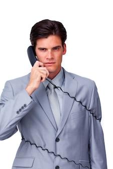 L'uomo d'affari infastidito si aggroviglia nei cavi del telefono