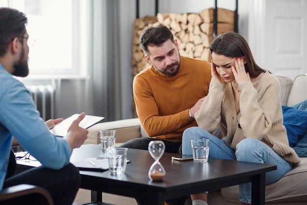 Coppie caucasiche infastidite dell'uomo e della donna che hanno conversazione con lo psicologo sulla sessione di terapia nella stanza leggera.