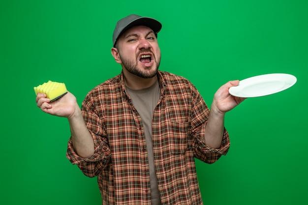 Uomo delle pulizie infastidito che tiene piatto e spugna
