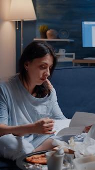 Infastidita giovane donna disperata seduta sul divano leggendo l'avviso di sfratto
