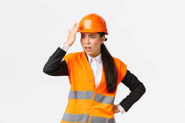 Infastidito e deluso capo ingegnere asiatico femminile che rimprovera i lavoratori edili facendo uno stupido errore, tocca il casco e sembra infastidito, arrabbiato con l'architetto, in piedi sfondo bianco