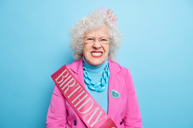 La signora anziana infastidita stringe i denti guarda con rabbia, esprime emozioni negative arriva alla festa di compleanno vestita con abiti alla moda