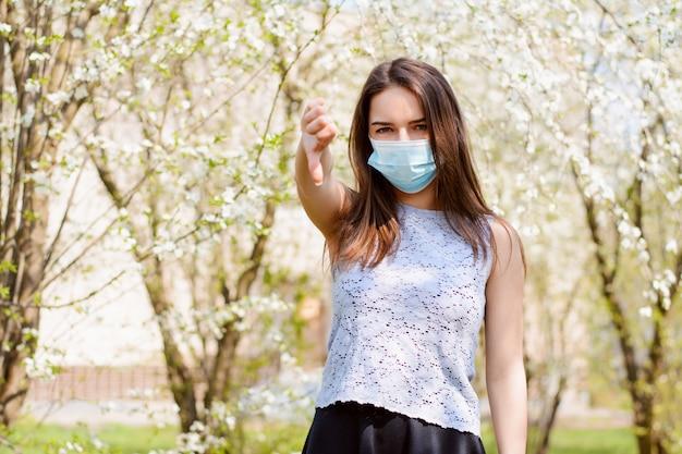 Ragazza infastidita stanting nel parco fiorito che mostra i pollici verso il basso, per mostrare la sua irritazione e antipatia per indossare costantemente una maschera medica per prevenire la diffusione del coronavirus