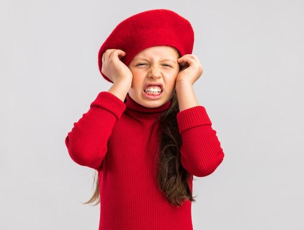 La piccola ragazza bionda infastidita che indossa un berretto rosso che tiene le mani sopra ha guardato la parte anteriore isolata sul muro bianco con spazio di copia