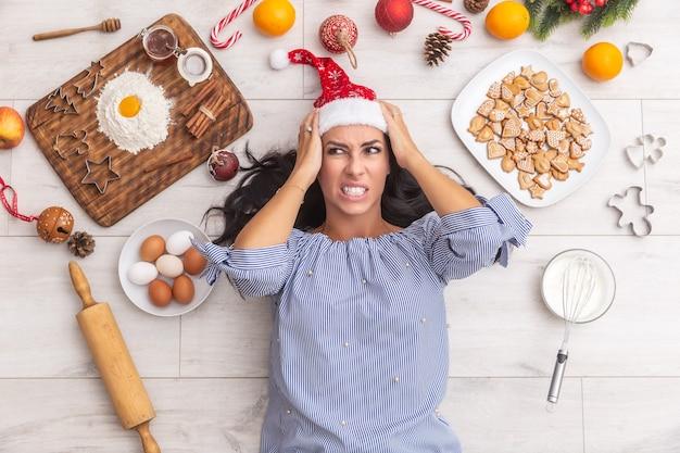 Madre infastidita che sembra arrabbiata a causa del troppo lavoro di natale che è tutto intorno a lei. pan di zenzero, forme da forno, frutta, farina, uova, mescolatore o rullo.