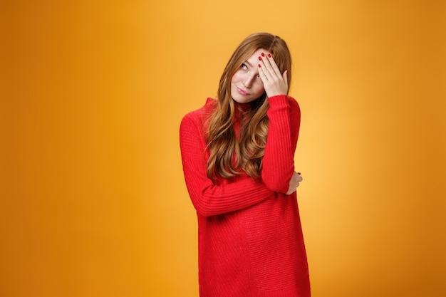 Donna imbarazzata infastidita e incazzata che si nasconde dietro la mano facendo il gesto del palmo che distoglie lo sguardo con un gesto irritato e umiliato, in piedi stufo e intenso su sfondo arancione.