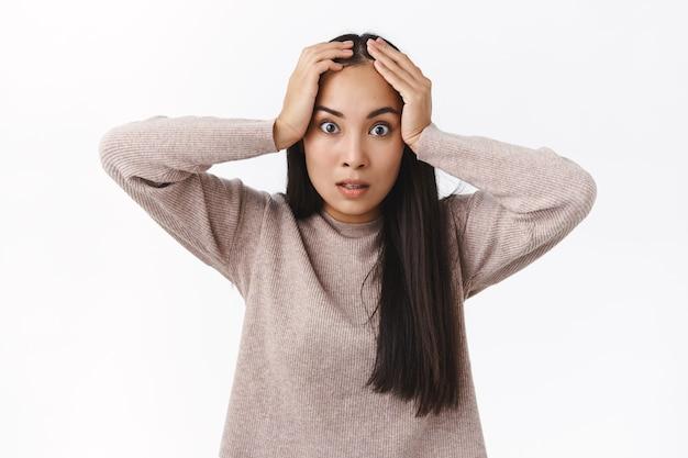 Fidanzata asiatica infastidita e sotto pressione, angosciata e stufo stanca di dire costantemente le stesse cose, afferrare la testa infastidita, fissare la telecamera intensamente, perdere la calma sensazione di stanchezza e irritazione, in piedi arrabbiato