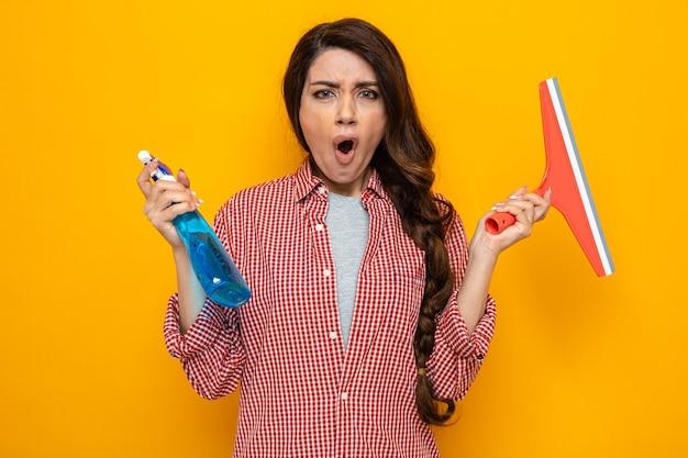 Una donna delle pulizie caucasica infastidita che tiene il tergipavimento e il detergente spray