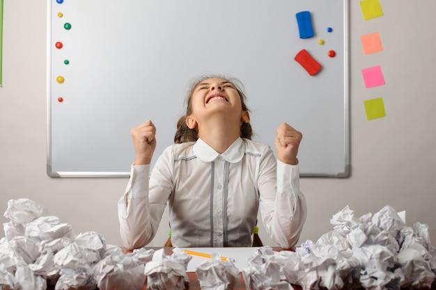 Studentessa infastidita che pensa intensamente alla composizione, non può scrivere nulla durante la lezione