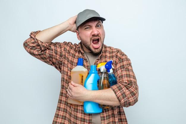 Uomo delle pulizie slavo infastidito che tiene in mano spray e liquidi per la pulizia