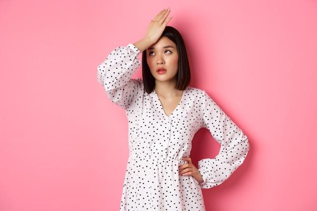Donna asiatica infastidita e stanca che fa facepalm, schiaffo anticipato e occhi al cielo delusi, in piedi in abito bianco su sfondo rosa.