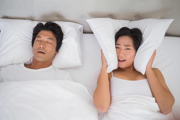 Donna infastidita che copre le orecchie con cuscini per bloccare russare