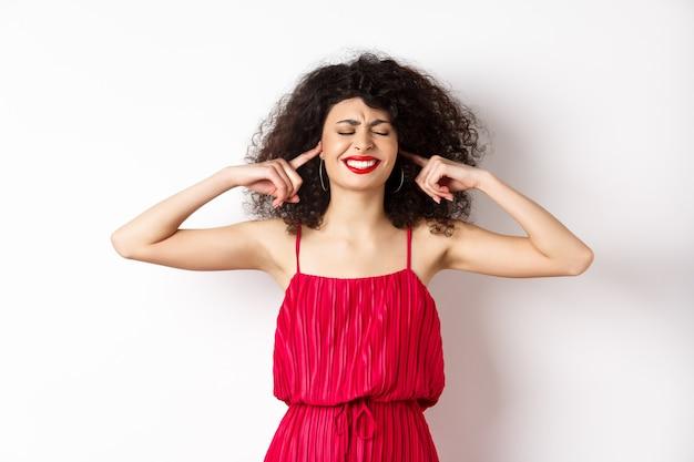 Donna infastidita con i capelli ricci e vestito rosso, chiudere gli occhi e le orecchie, bloccare il suono fastidioso, stringere i denti infastiditi, lamentarsi della musica ad alto volume o dei vicini, in piedi su sfondo bianco.