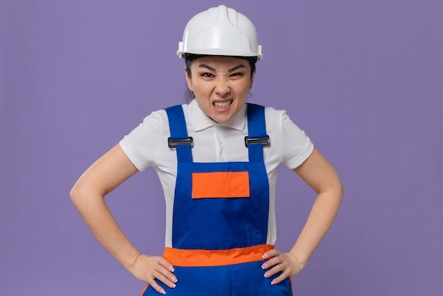 Giovane donna asiatica infastidita del costruttore con il casco di sicurezza bianco che mette le mani sulla sua vita e che guarda