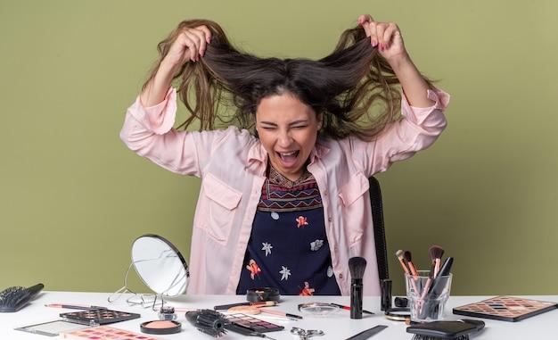 Infastidita giovane ragazza bruna seduta al tavolo con strumenti per il trucco che le tengono i capelli
