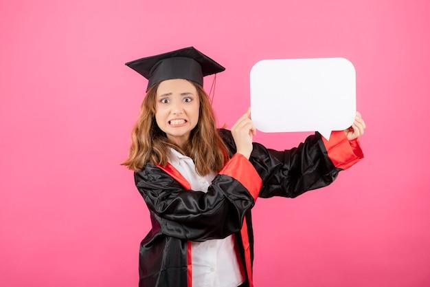 Ragazza infastidita che tiene in mano una lavagna bianca e indossa un abito da laurea sulla parete rosa