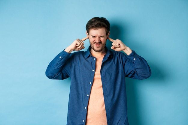 Il giovane infastidito blocca il suono, chiude le orecchie con le dita e fa smorfie, disturbato dalla musica ad alto volume, in piedi su sfondo blu.