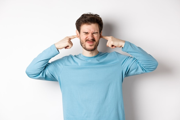 Giovane infastidito tappare le orecchie da un suono forte e terribile, essere disturbato da un rumore fastidioso, fare smorfie scontente, in piedi su sfondo bianco