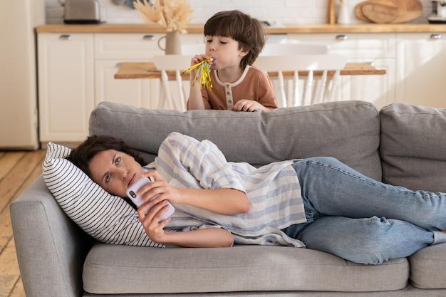 Infastidita giovane mamma che alza gli occhi al cielo stanca del ragazzino rumoroso, la giovane madre stanca cerca di rilassarsi dopo il lavoro