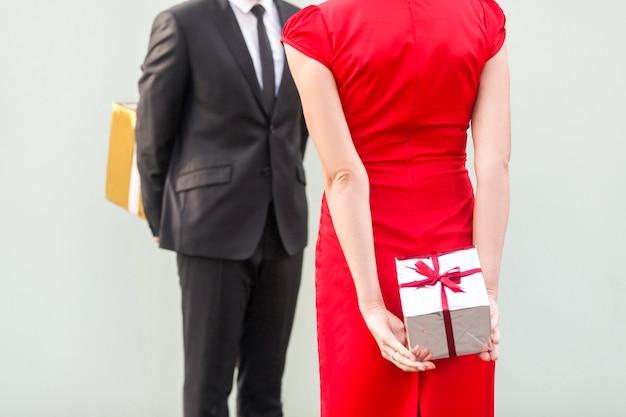 Coppia anonima in piedi l'un l'altro e tenendo una scatola regalo dietro la colonna vertebrale