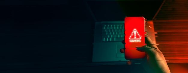 Un hacker anonimo e utilizza un malware con telefono cellulare per hackerare password dati personali e denaro dai conti bancari. il concetto di cyber crime.